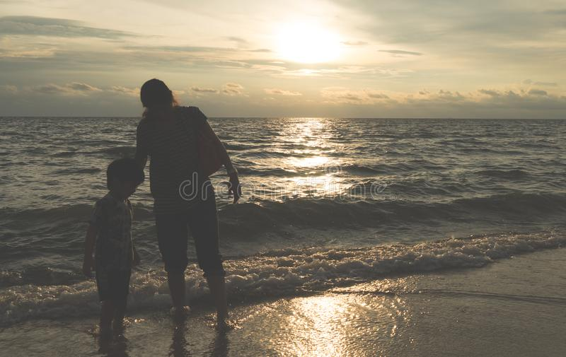 Mime a tomar a su niño en un paseo en una silueta de la playa de la puesta del sol imagen de archivo