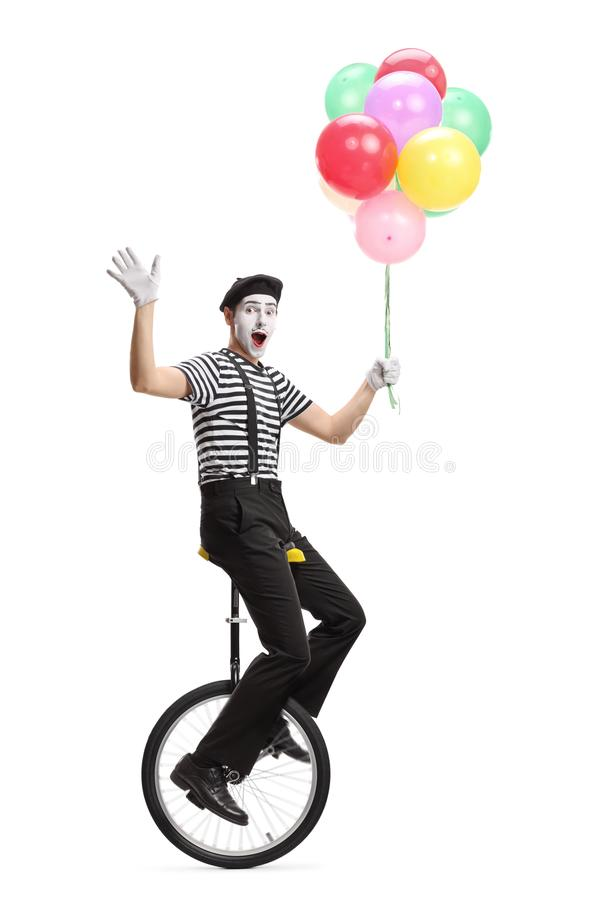 Mime on a unicycle holding a bunch of colorful balloons and waving at the camera royalty free stock image