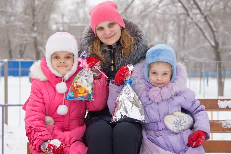 Mime y dos hijas con los regalos de la Navidad en sus manos fotografía de archivo