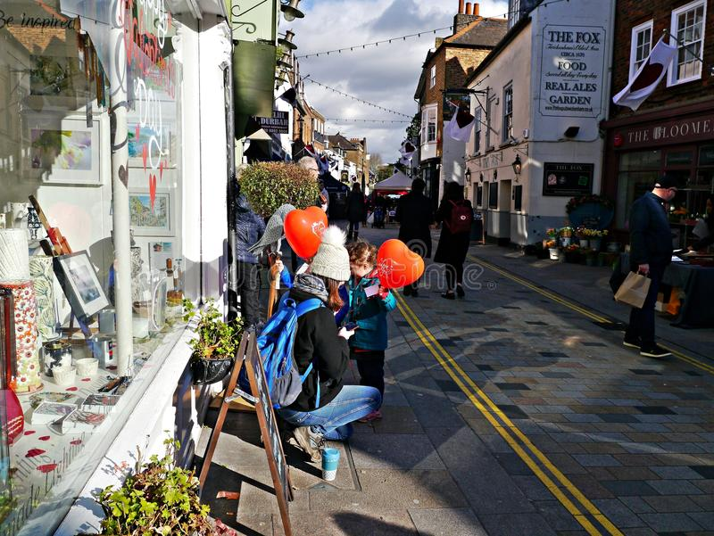 Mime y dos niños que sostienen los globos rojos de la forma del corazón en Twickenham Reino Unido imagenes de archivo