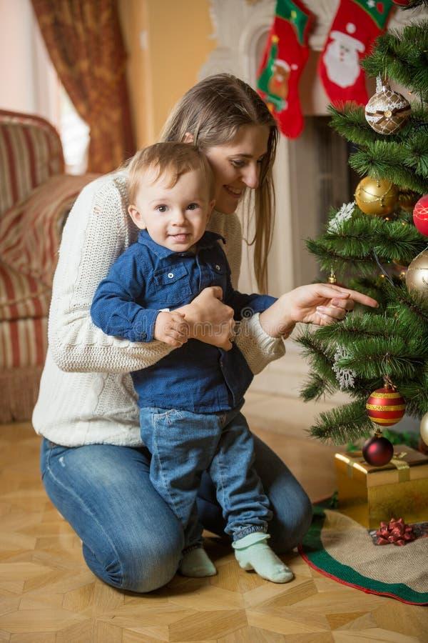 Mime y 10 meses del bebé que adorna el árbol de navidad en h fotografía de archivo