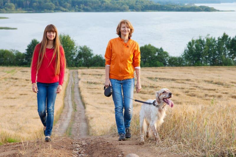 Mime y su hija con el perro que camina al aire libre imagen de archivo libre de regalías