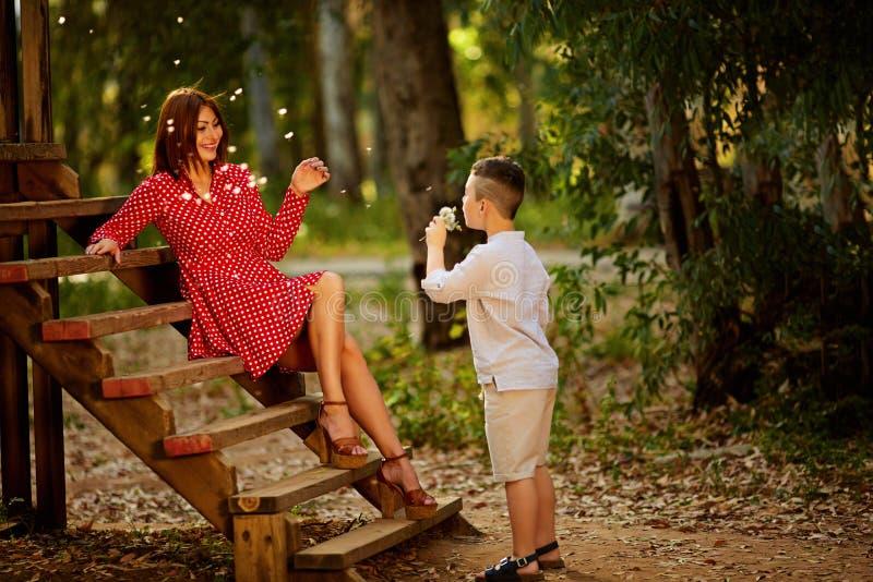 Mime y su niño que juega en campo de la primavera en luz del sol suave imagenes de archivo
