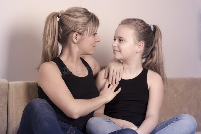 Mime y su pequeña hija que se sienta en el sofá y que mira uno a imagenes de archivo