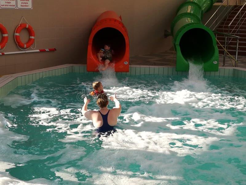 Mime y sus dos niños a las diapositivas en la piscina fotos de archivo