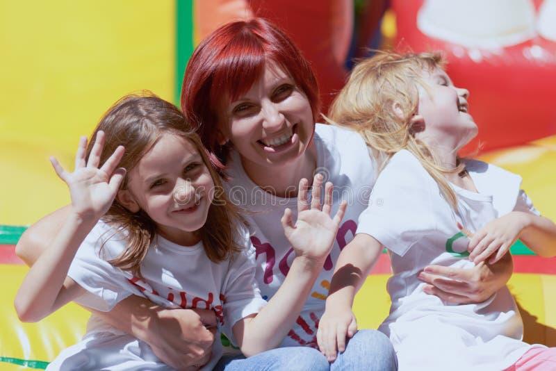Mime y sus hijas que se divierten en castillo de salto fotografía de archivo libre de regalías