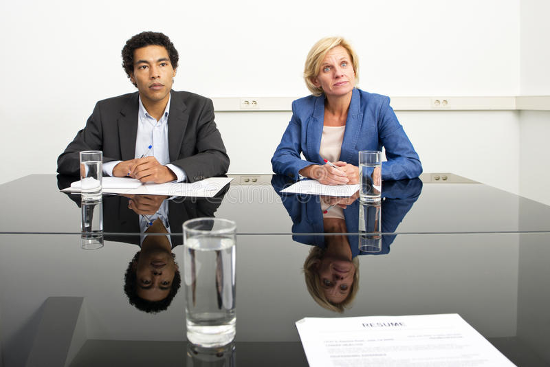 Mimicking body language. Two managers, mimicking body language and playing a psychological game during a stern job - or appraisal - interview royalty free stock image