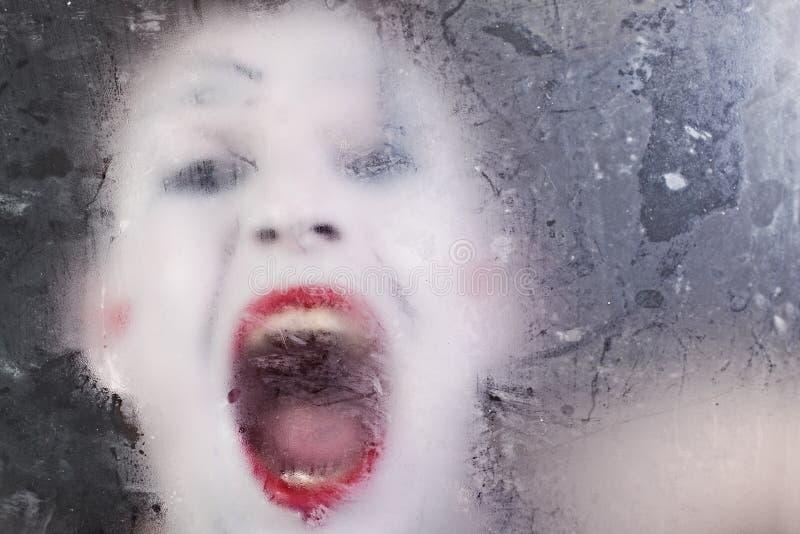 Mimo di grido del fronte spaventoso per vetro oscuro fotografia stock libera da diritti