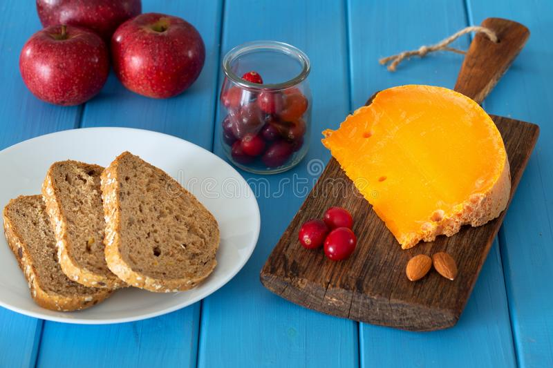 Mimolette, type of cheese together with the addition of bread a. Nd fresh cranberries royalty free stock images