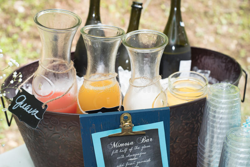 Mimosa Bar. A mimosa bar with a selection of fresh fruit juices and prosecco at an outdoor party royalty free stock image
