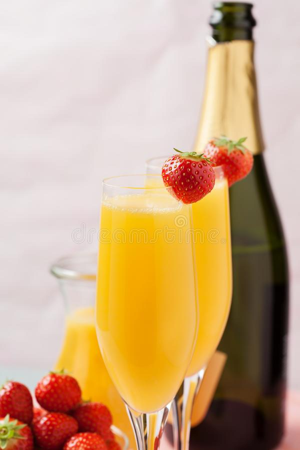 Mimosa cocktail and strawberries. Two glasses of mimosa cocktail champagne with orange juice and fresh strawberries stock photos