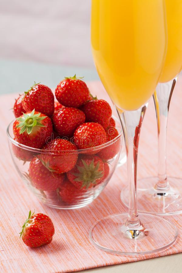Mimosa cocktail and strawberries. Two glasses of mimosa cocktail champagne with orange juice and fresh strawberries royalty free stock image