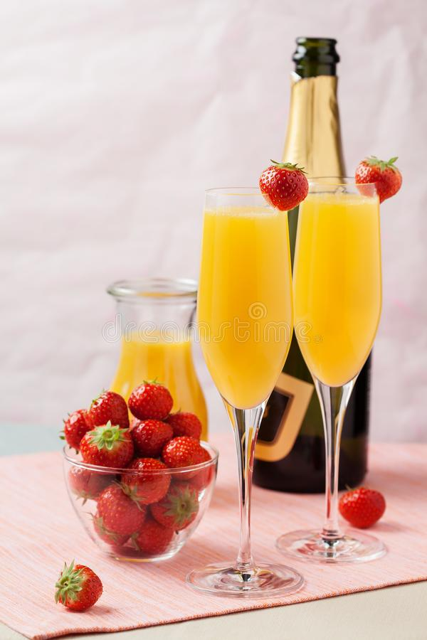 Mimosa cocktail and strawberries. Two glasses of mimosa cocktail champagne with orange juice and fresh strawberries royalty free stock photos