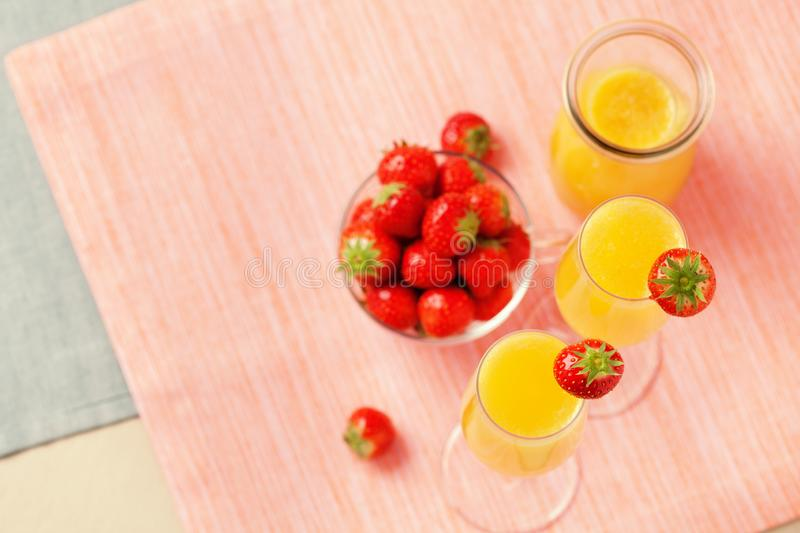 Mimosa cocktail and strawberries. Two glasses of mimosa cocktail champagne with orange juice and fresh strawberries stock images