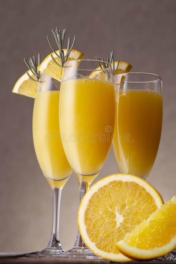 Mimosa cocktails. In champagne glasses with orange juice and sparkling wine decorated with lavender leaves and orange slices stock image