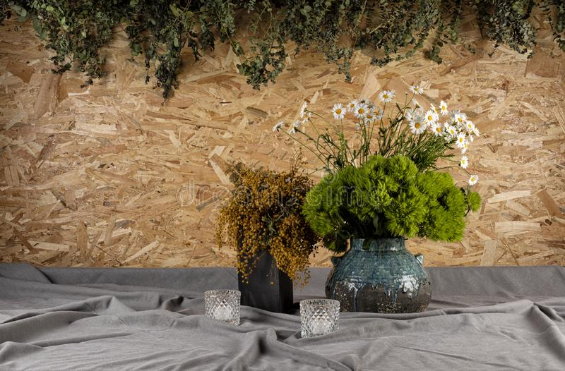Mimosa, daisy margarite in vase on wooden table. Leaves dangling from the OSB board in the background stock images