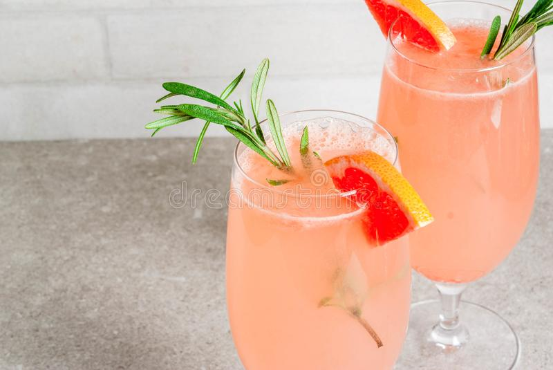 Mimosa drink for Christmas party. Festive drink for Christmas party, Mimosa cocktail with Champagne, Grapefruit and Rosemary, on stone tale, copy space stock photography
