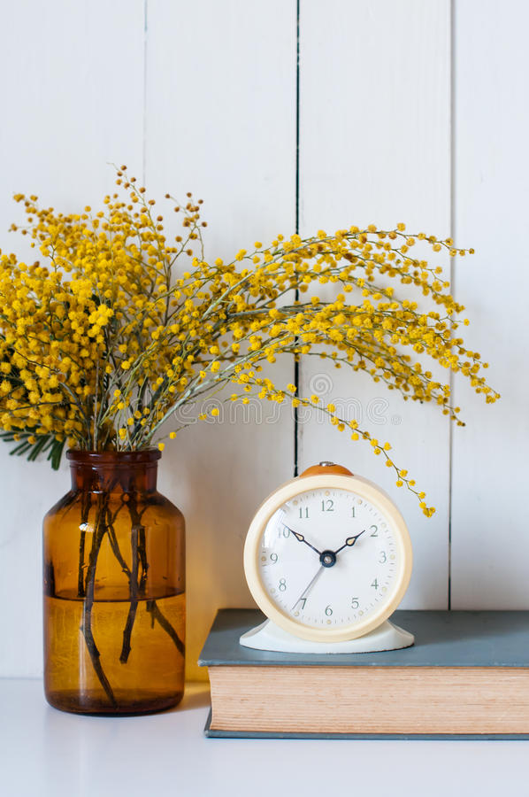 Mimosa. Home decor, mimosa yellow spring flowers in a vintage bottle, book and alarm clock on the white wall background royalty free stock images