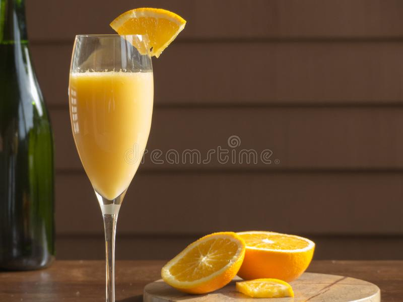 Mimosa, Orange Slices & Champagne Bottle. A mimosa in a champagne glass with a slice of orange placed on the edge, pieces of orange below and a champagne bottle stock image
