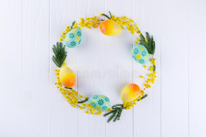 Mimosa and painted aggs circle frame on white background . Space for text. Floral background royalty free stock photos
