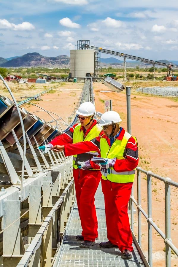 Minério da platina do transporte de correia transportadora para processar com os inspetores da segurança de mineração que verific imagem de stock