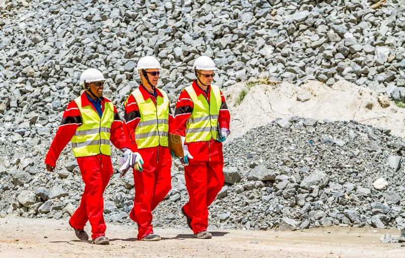 Minério da platina do transporte de correia transportadora para processar com os inspetores da segurança de mineração que verific foto de stock