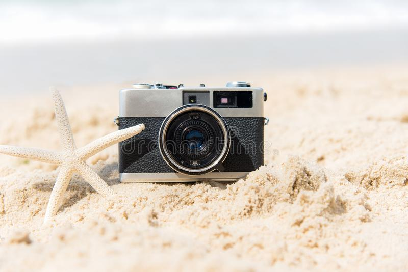 min andra ser sommarsemesterarbeten Gammal kamera för tappning av turism på den sandiga stranden med stjärnafisken royaltyfri fotografi