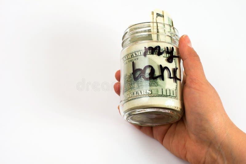 Min bank som är skriftlig på en krus i hand med dollarsedlar Besparing- och hemfinansbegrepp arkivfoton