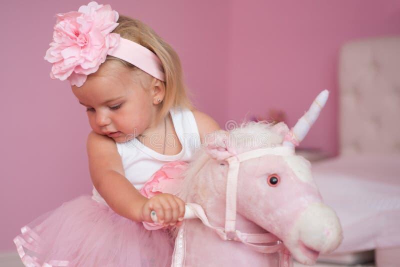 Min favorit- leksak Liten flicka med den långa frisyren Liten blond häst för flickarittleksak Musikband för småbarnkläderhår hår royaltyfri bild