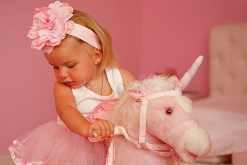Min favorit- leksak Liten flicka med den långa frisyren Liten blond häst för flickarittleksak Musikband för småbarnkläderhår hår royaltyfri foto