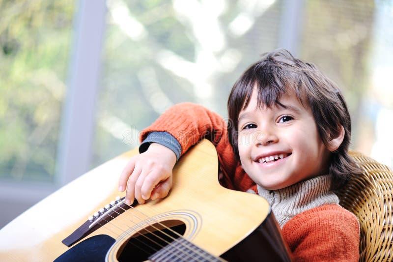Min son som spelar gitarren arkivfoto