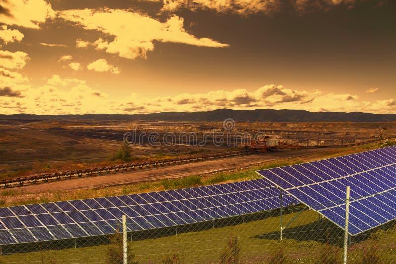 Mina de carvão com os painéis da energia solar no por do sol foto de stock