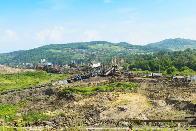 Mina de carvão enorme do poço aberto feita com máquinas escavadoras, os carregadores, os caminhões e as máquinas de empilhamento  fotografia de stock royalty free