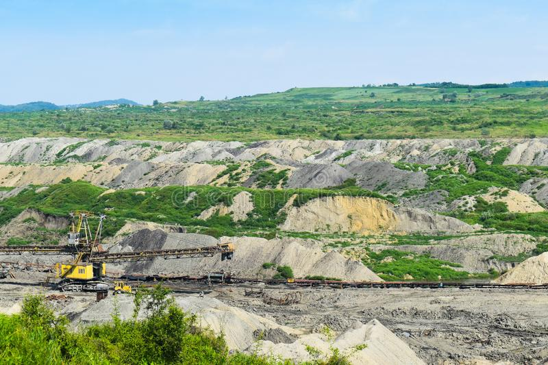 Mina de carvão enorme do poço aberto feita com máquinas escavadoras, os carregadores, os caminhões e as máquinas de empilhamento  fotos de stock