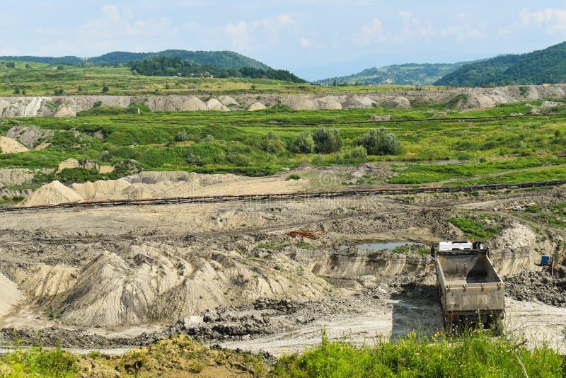 Mina de carvão enorme do poço aberto feita com máquinas escavadoras, os carregadores, os caminhões e as máquinas de empilhamento  foto de stock royalty free