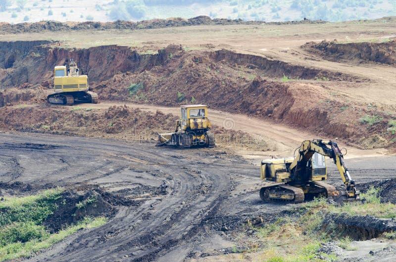 Mina de la explotación minera a cielo abierto con las porciones de maquinaria en el trabajo imágenes de archivo libres de regalías