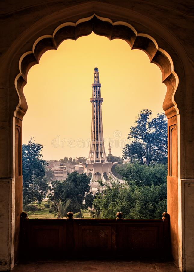 Minar e pakistan from badshahi mosque corridor. Minar-e-Pakistan is a public monument located in Iqbal Park, adjacent to the Walled City of Lahore, in the royalty free stock photo