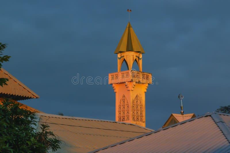 Minaret de la mosquée dans les rayons oranges du coucher du soleil contre le ciel foncé images libres de droits