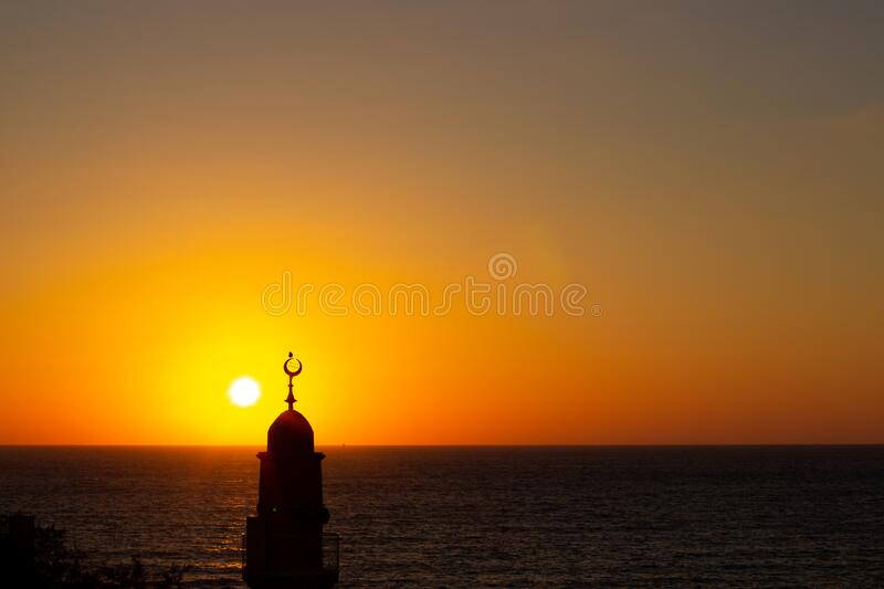 Minaret Eastern architecture religion building tower on vivid orange sunset sky above Mediterranean sea horizon background. Wallpaper pattern scenic view with royalty free stock image