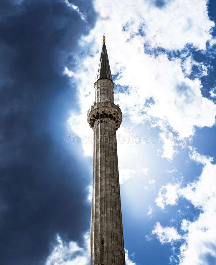 Minaret of an Islamic mosque photographed from below against a dramatic sky with clouds. royalty free stock images