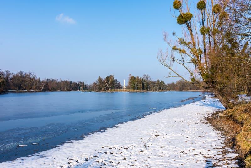 Minaret på den Lednice slotten, historiskt ställe för TjeckienUNESCO, sjön i förgrund arkivfoton