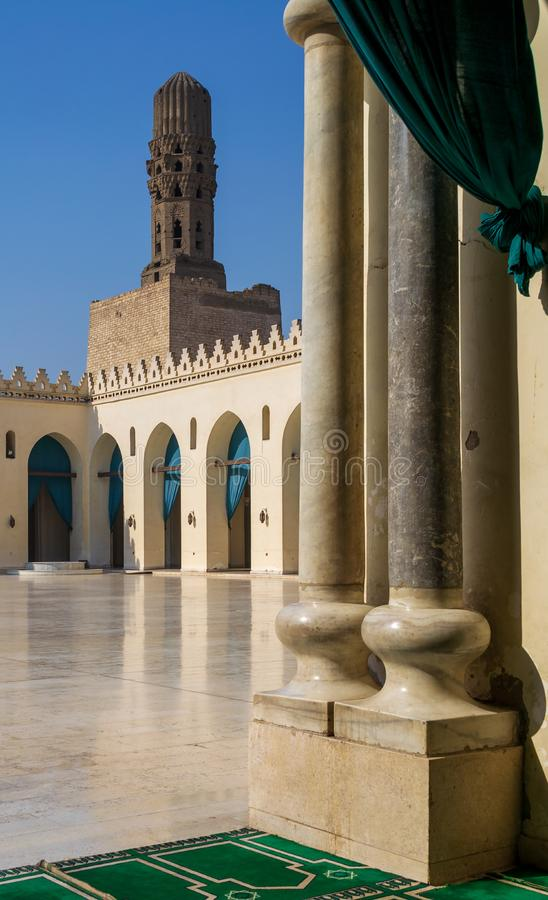 Minaret of public historic Al Hakim Mosque framed by two marble columns, Moez Street, Cairo, Egypt. Minaret of public historic Al Hakim Mosque known as The stock photos