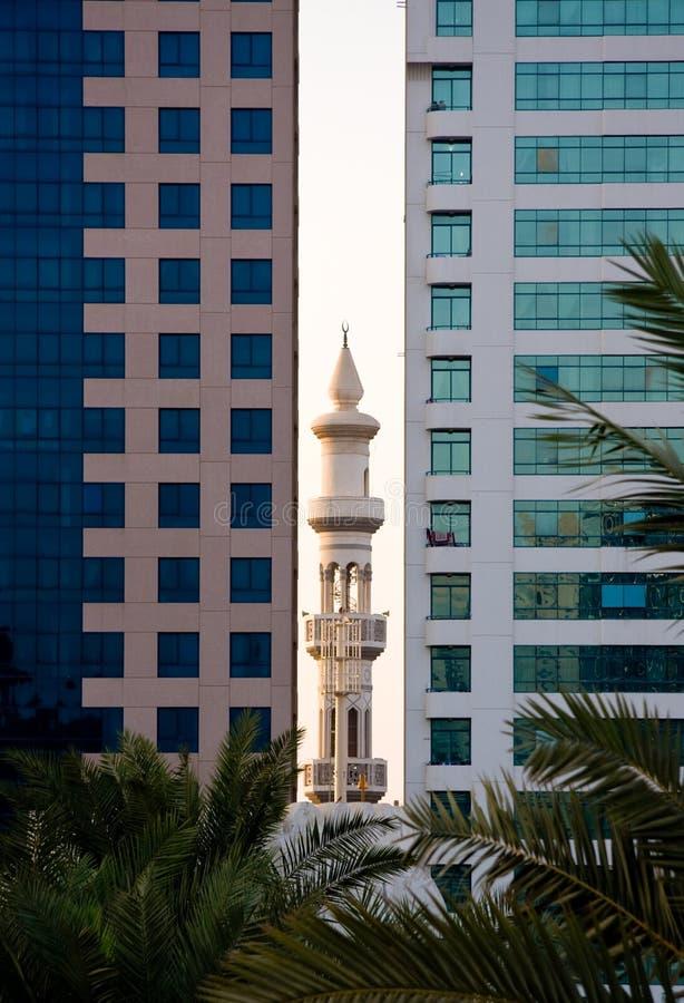 Minarete que peeping entre prédios de escritórios imagens de stock