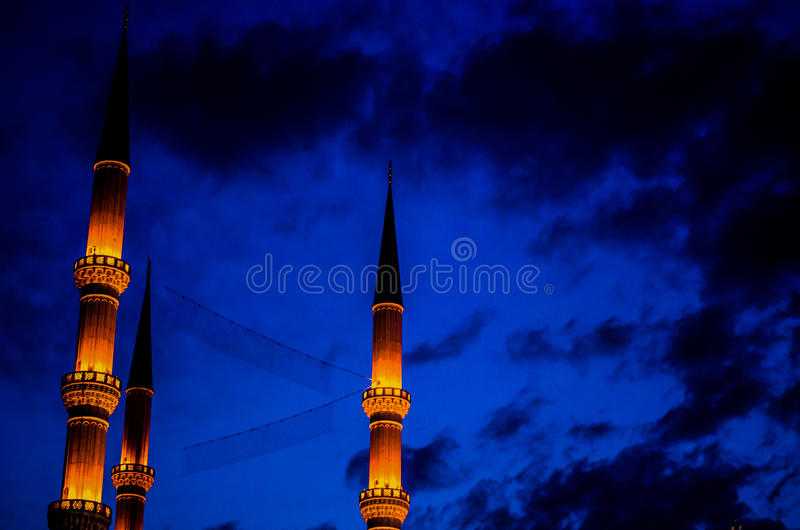 Minarets rising through the blue night of Istanbul, Turkey. Mosque`s minarets with a dark cloudy sky in the blue night of Istanbul, Turkey stock image