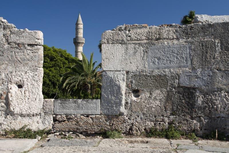 Minarettoren en kasteelmuur in Kos-stad royalty-vrije stock afbeeldingen