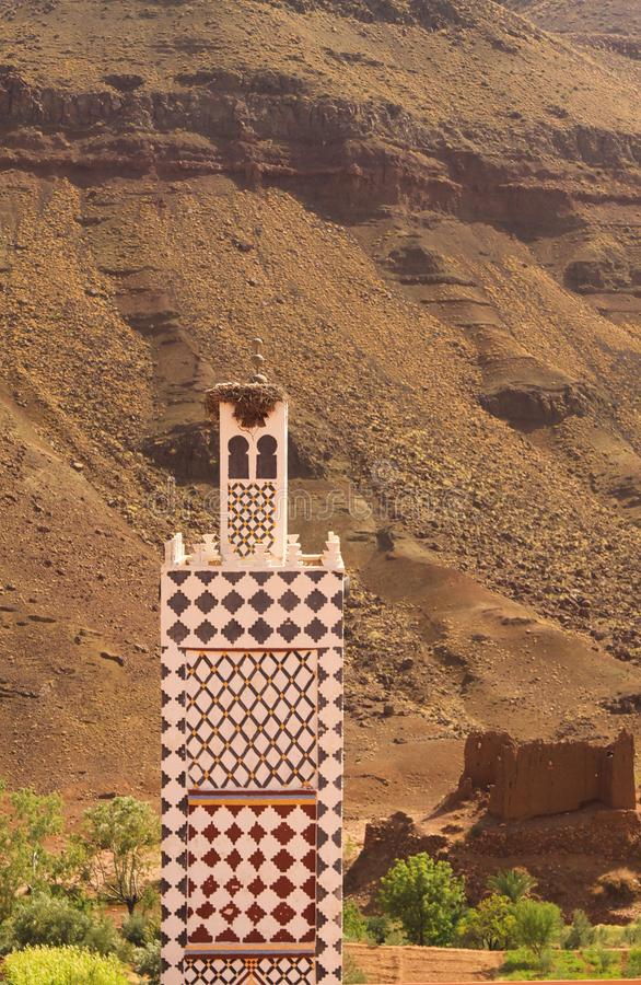 Minarettturm gegen schroffe Gebirgswand in den Atlasbergen - Marokko stockfoto