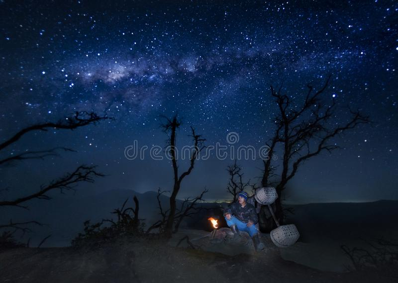Minatore dello zolfo di Kawah Ijen che riposa sotto l'albero dopo la finitura delle sue attività di estrazione mineraria per fotografie stock