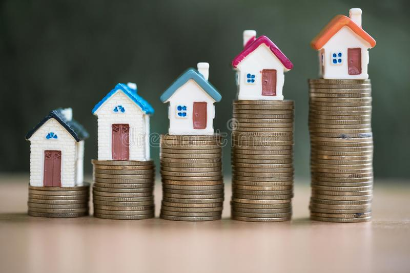 Minature houses resting on coin stacks, concept for property ladder, mortgage and real estate investment.  stock images