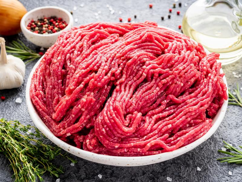 Mince beef, ground meat with ingredients for cooking on dark gray background, side view, close up royalty free stock photography