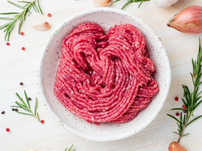 Mince beef, ground meat with ingredients for cooking on white wooden rustic table, top view royalty free stock photography